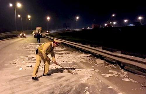 Tổ công tác cảnh sát giao thông, thay nhau đứng ra phân luồng và mượn chổi, xẻng quét dọn đá rơi vãi trong đêm.Ảnh: Nguyên Dân.