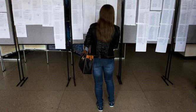 Một phụ nữ xem kết quả thi đầu vào dán trên bảng thông báo của Đại học Donetsk, miền đông Ukraine, hôm 25/9. Ảnh: AFP.