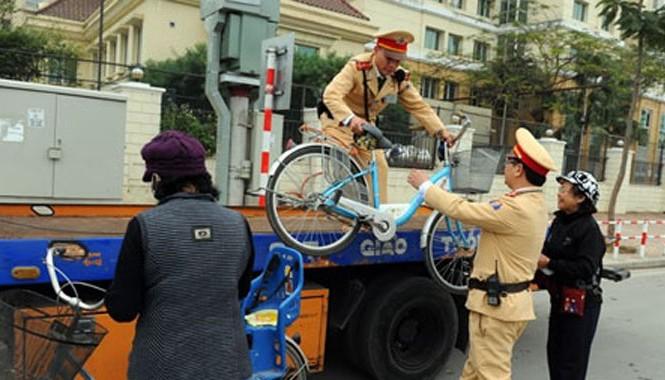 Hai đồng chí Đỗ Thanh Tùng và Lê Ngọc Tùng sử dụng xe chuyên dụng để đưa 2 cụ bà qua cầu Nhật Tân.