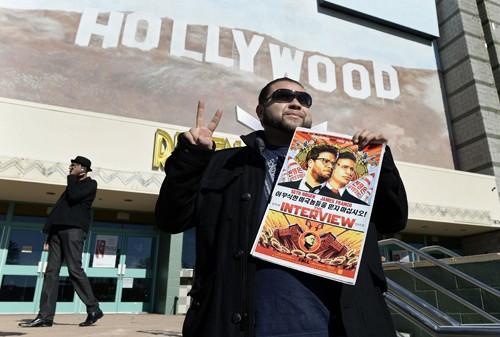 Một khán giả cầm poster phim The Interview trước rạp phim ở Los Angeles, California vào ngày công chiếu 25/12. Ảnh: Reuters.