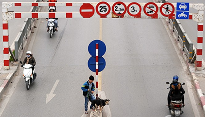 Người đi bộ qua cầu vượt Láng Hạ bất chấp biển cảnh báo ngay trước mặt.