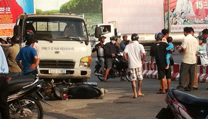 Xe ô tô tải cuốn xe gắn máy dưới gầm.