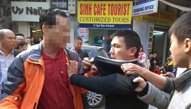 Anh Tuấn (áo khoác cam) dũng cảm khống chế tên cướp áo đen. Ảnh: Facebook Vu Tuan Anh.