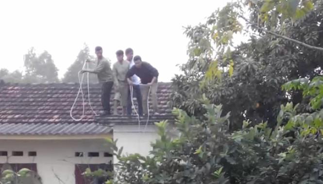 """Người dân phải đứng trên nóc nhà, quăng dây xuống nhằm giăng bẫy bắt """"trâu điên"""". Ảnh cắt từ clip do nhân chứng cung cấp."""