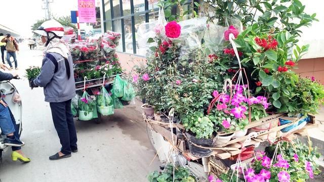 Chị Hoa đang bán hoa dạo trên đường Nguyễn Xiển. Ảnh:H.N.