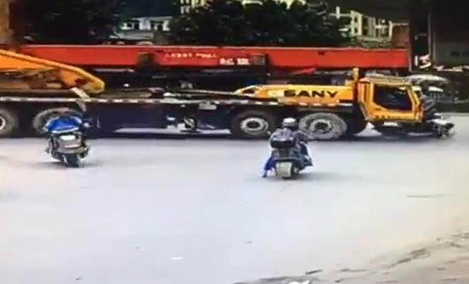 Xe tải siêu trường cuốn người đi xe máy vào gầm