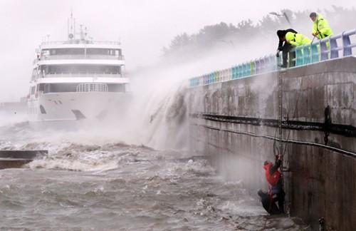 Các thuyền viên được giải cứu sau khi bị sóng cuốn khỏi cầu cảng ở miền nam Hàn Quốc. Ảnh: Yonhap.