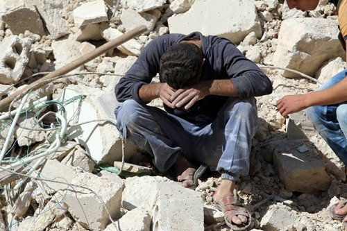 Một người đàn ông mất đi người thân sau một đợt không kích ở khu al-Qaterji, Aleppo, ngày 11/10. Ảnh: Reuters.