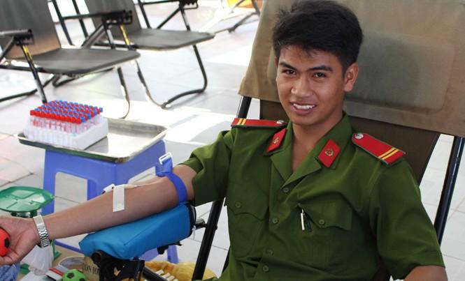 Chiến sỹ công an tươi cười hiến máu.
