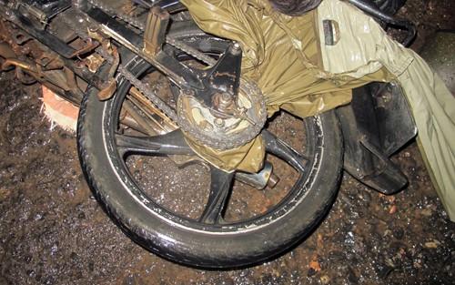 Áo mưa bị cuốn vào bánh sau xe, siết cổ nạn nhân tử vong. Ảnh: Khánh Hương.
