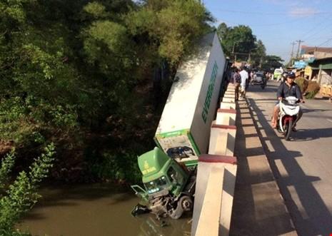 Chiếc xe container đâm sập lan can cầu rồi rơi xuống sông. Ảnh: CTV