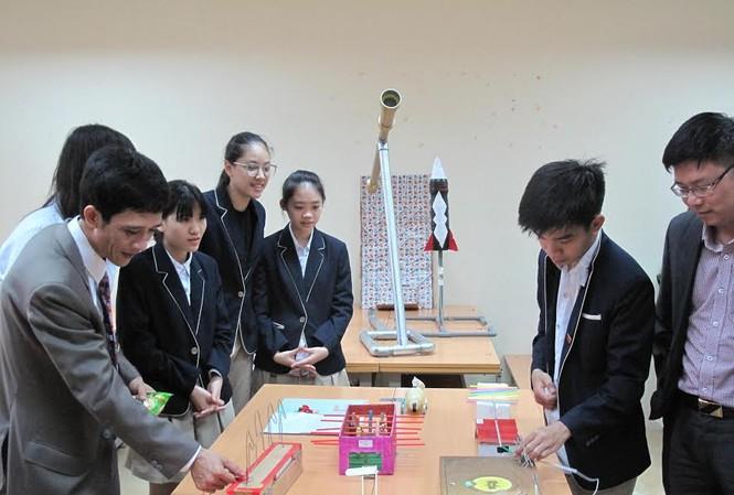 Học sinh và giáo viên trường THPT Phan Huy Chú đang thử nghiệm một sản phẩm của học sinh liên quan đến vật lý - ảnh Nghiêm Huê