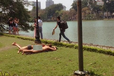 Hai nữ du khách mặc bikini tắm nắng bên Hồ Gươm