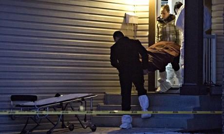 Đưa nạn nhân ra khỏi căn nhà nơi xảy ra vụ sát hại (Ảnh: AP)