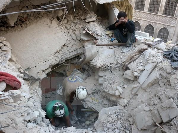 Tình nguyện viên Syria tìm kiếm người bị mắc kẹt trong những đống đổ nát sau một vụ không kích tại Aleppo ngày 4/10. (Nguồn: AFP/TTXVN)