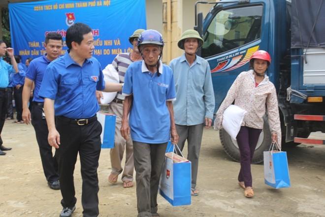 Anh Trần Anh Tuấn (Phó bí thư thường trực Thành Đoàn Hà Nội) trao quà cho người dân xã Phúc Đồng (huyện Hương Khê, Hà Tĩnh).