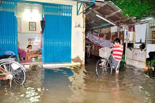 Người dân bất lực nhìn nước ngập tràn vào nhà. Ảnh: Ngô Bình