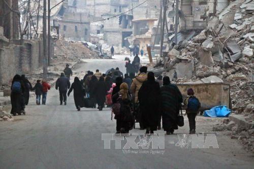 Người dân Syria rời khỏi khu vực Sukkari để đến khu vực an toàn hơn do quân nổi dậy chiếm giữ ở đông nam thành phố Aleppo ngày 12/12. Ảnh: AFP/TTXVN.