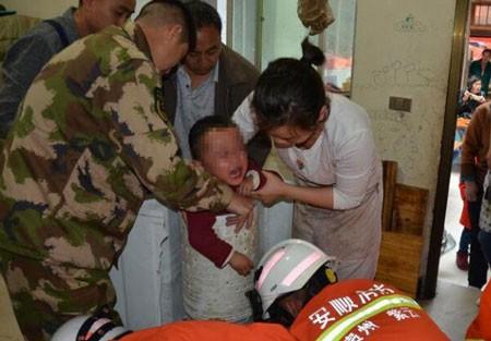 Em bé 3 tuổi bị mắc kẹt trong phần sấy của máy giặt.Ảnh: Shanghaidaily