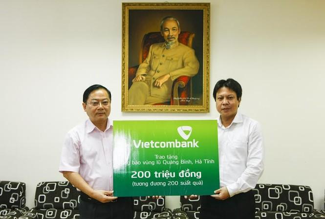 Đại diện Công đoàn Ngân hàng Vietcombank (bên phải) trao số tiền 200 triệu đồng đến bà con vùng lũ qua báo Tiền Phong. Ảnh: Như Ý