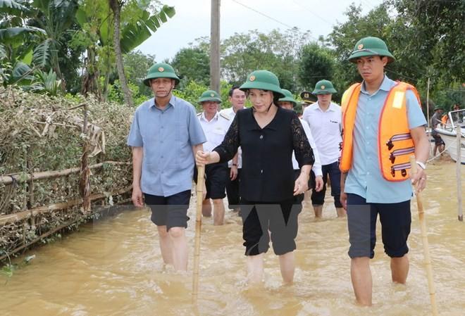 Chủ tịch Quốc hội Nguyễn Thị Kim Ngân đi thị sát tại xã Đức Hưng, huyện Vũ Quang vẫn đang ngập trong lũ. (Ảnh: Trọng Đức/TTXVN)