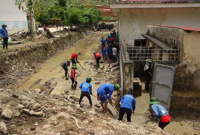 Các tình nguyện viên dọn dẹp bùn đất khu vực trường học và nhà sinh hoạt cộng đồng