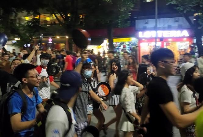 Nhiều người trẻ cầm chảo, đội mũ bảo hiểm đi trên phố (Ảnh: X.T)