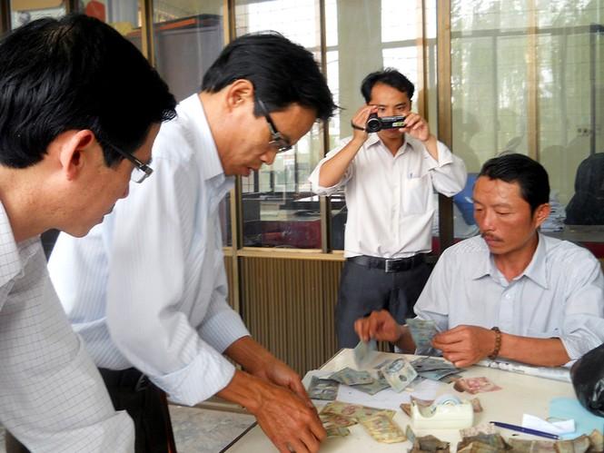 Cán bộ Ngân hàng Nhà nước kiểm tra số tiền bị cháy của tiểu thương Lương Hồng Thắng
