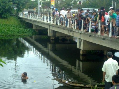 Người dân hiếu kỳ xem lực lượng chứng năng truy tìm hung khí do Tài, Triệu giết người vứt bỏ xuống sông