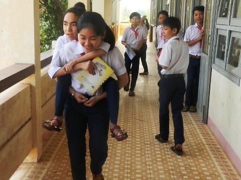 Ở trường, bạn bè vẫn thường giúp đỡ cõng Thủy khi cần phải đi lại