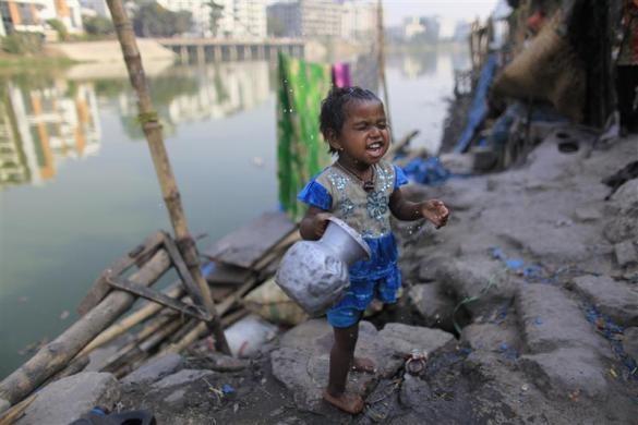Một bé gái ba tuổi đang nghịch nước tại khu ổ chuột thủ đô Dhaka, Bangladesh. Ảnh: Reuters