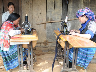 Chị Lý Thị Tàng – vợ nạn nhân Hảng A Sú đang hướng dẫn con may áo