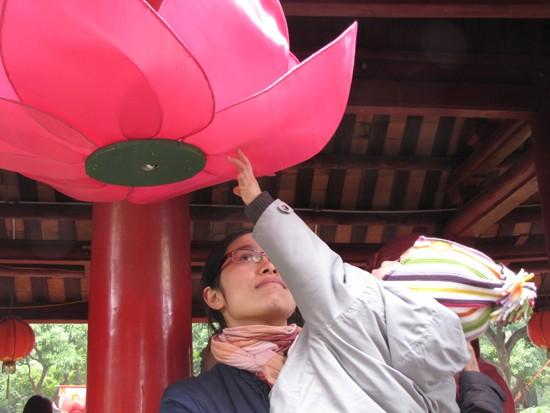 Một em bé thích thú với chiếc đèn lồng đỏ trang trí trong Văn Miếu