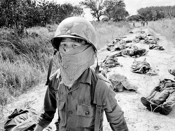 Bức ảnh lịch sử: Người lượm xác phải che mặt vì mùi hôi thối từ xác binh lính Mỹ và Việt Nam bị chết trong trận chiến ở nhà máy cao su Michelin (Dầu Tiếng) cách Sài Gòn 45 dặm về phía đông bắc.             Ảnh chụp ngày 27-11-1965. Tác giả: Horst Faas