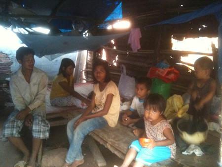 Vợ chồng chị Xuân ngồi trong túp lều của gia đình mình