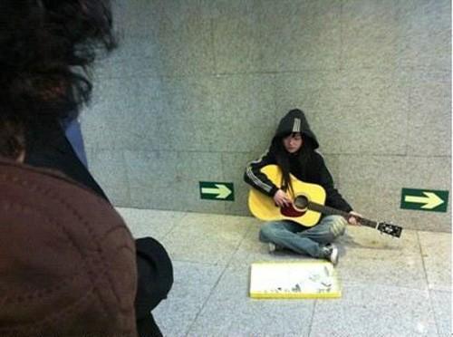 Hình ảnh cô gái xinh đẹp đánh đàn xin tiền bên lề phố khiến nhiều người động lòng