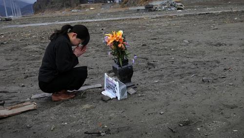 Cô Mika Hashikai, 37 tuổi đang cầu nguyện cho người cha quá cố đã mất tích trong thảm họa năm 2011