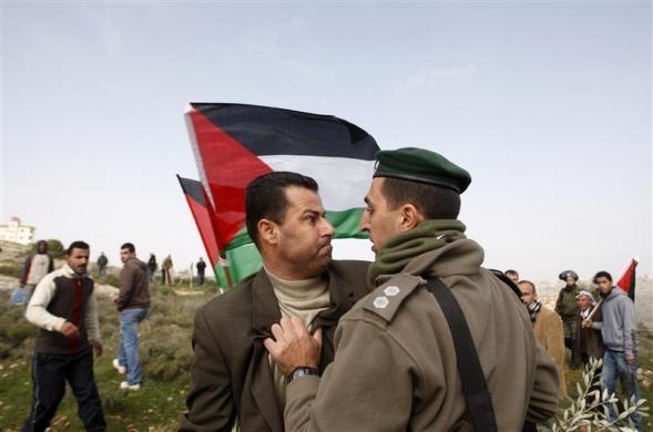 Tại vùng biên giới Israel, một nhà hoạt động Palestine và một sĩ quan quân đội đang tranh ẩu đả nhau vào ngày 8-2. Tại làng al-Janiya, gần Ramallah, các cuộc biểu tình vẫn đang xảy ra. Ảnh: Reuters