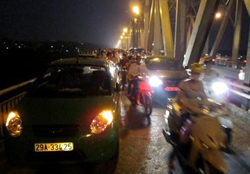Taxi 4 chỗ màu xanh chở nam thanh niên đỗ sát thành, hướng từ nội thành sang Gia Lâm. Ảnh: Hoàng Việt.