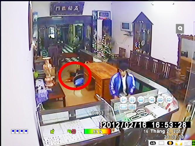Tên cướp dùng cùi chỏ tay phá kính cướp vàng nhưng bất thành. Ảnh chụp từ clip