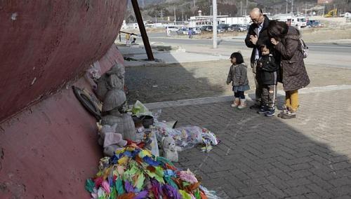 Một gia đình đang cầu nguyện cho các nạn nhân thảm họa sóng thần năm 2011 tại cảng Kesennuma