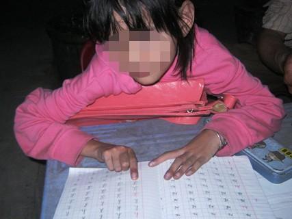 Bé gái tên Vân (nhà ở Q.12, TPHCM), ngồi trước nhà làm học viết, học đọc sau khi từ lớp học chữ về. Tháng 9 tới, Vân mới vào lớp 1. (Ảnh: Hoài Nam)