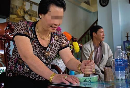 Một người phụ nữ Việt Nam dùng miếng sừng tê giác mài vào bát đựng ít nước và tin rằng bột sừng chữa được sỏi thận.