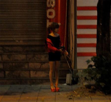Một gái mại dâm đứng chờ khách trên đường