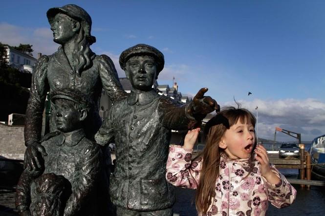 Bé gái đứng bên bức tượng tưởng niệm chào đón đoàn tàu chở 1.309 hành khách tại Cobh.