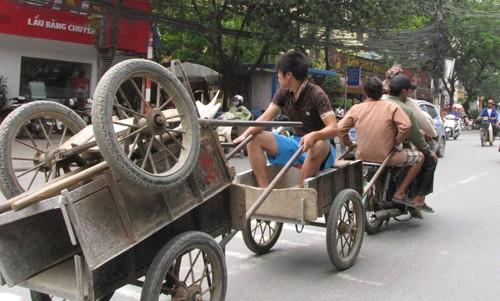 Bốn thanh niên trên một chiếc xe máy cà tàng, kéo theo một người nữa và ba chiếc xe thồ. Ảnh: Trường Phong..
