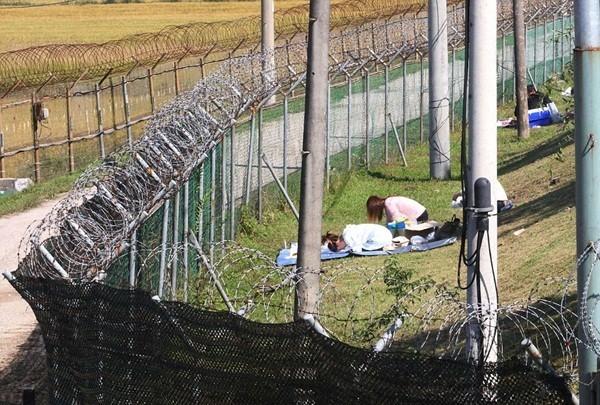 2 người phụ nữ đang cúng bái trong khu đất có đường dây điện bao quanh