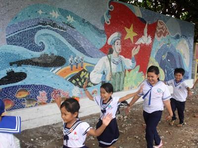 Trẻ nhỏ trên đảo chơi cạnh các bức tường gốm được xây dựng đồng thời với lá cờ