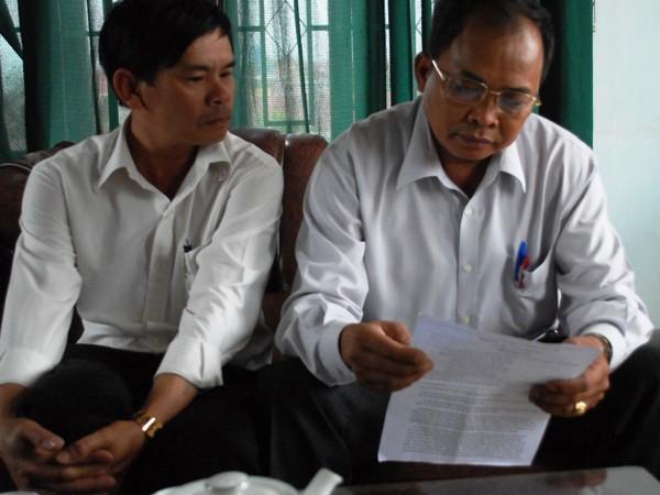 Ông Nguyễn Quang Sanh (phải) đang đọc đơn tố cáo