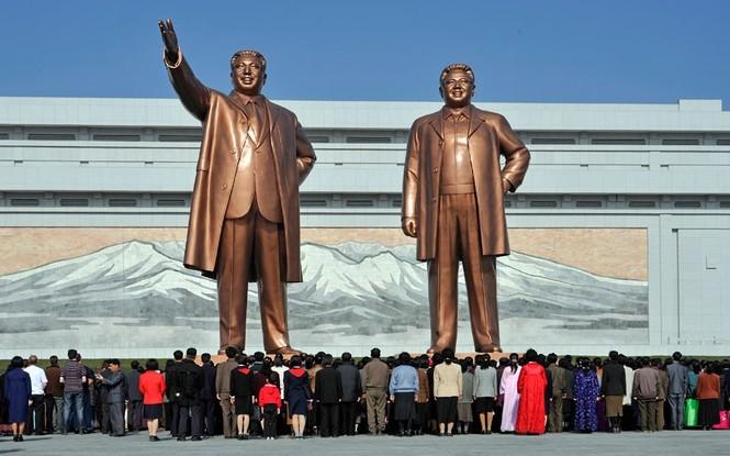"""Người dân Triều Tiên thể hiện sự tôn kính trước 2 bức tượng khổng lồ của cố chủ tịch Kim Nhật Thành và Kim Jong-il.             """"Trong suốt hành trình di chuyển trên xe bus luôn có 3 bảo vệ đi cùng, họ yêu cầu chúng tôi không được chụp ảnh khu vực bên trong nhiều di tích như đài tưởng niệm"""", nhiếp ảnh gia Bergman nói"""